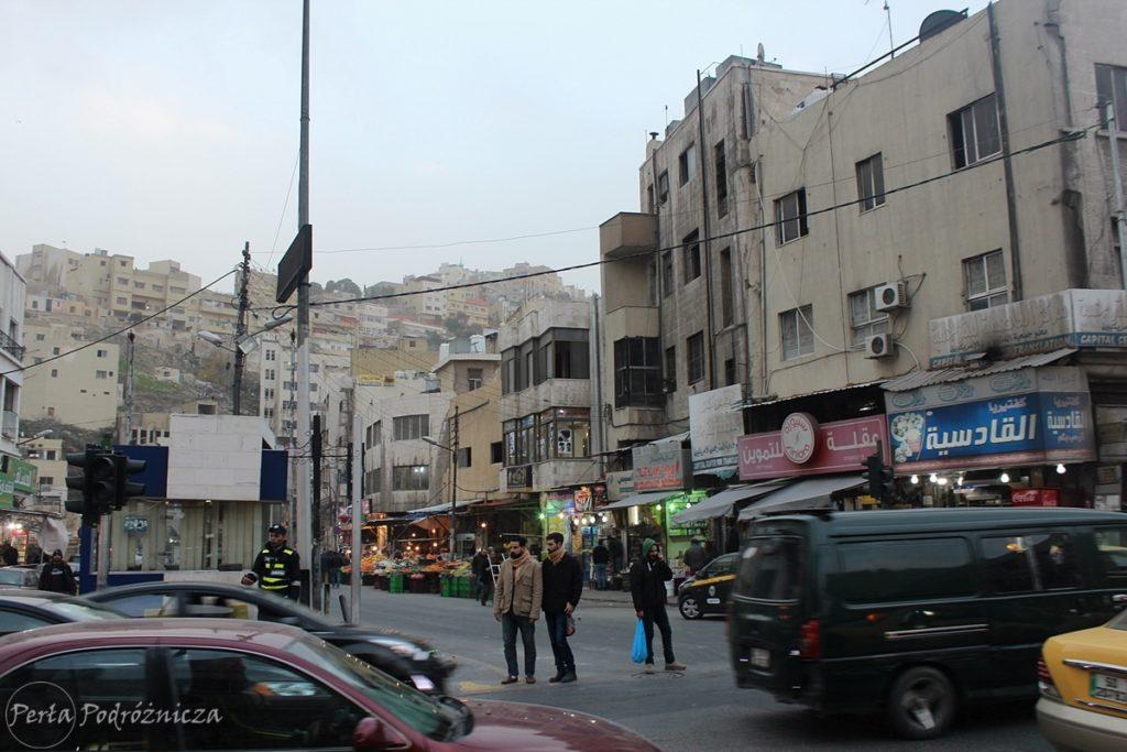 Toczące się życie na ammańskiej ulicy - ruch samochodowy, przechodnie, policjant na służbie